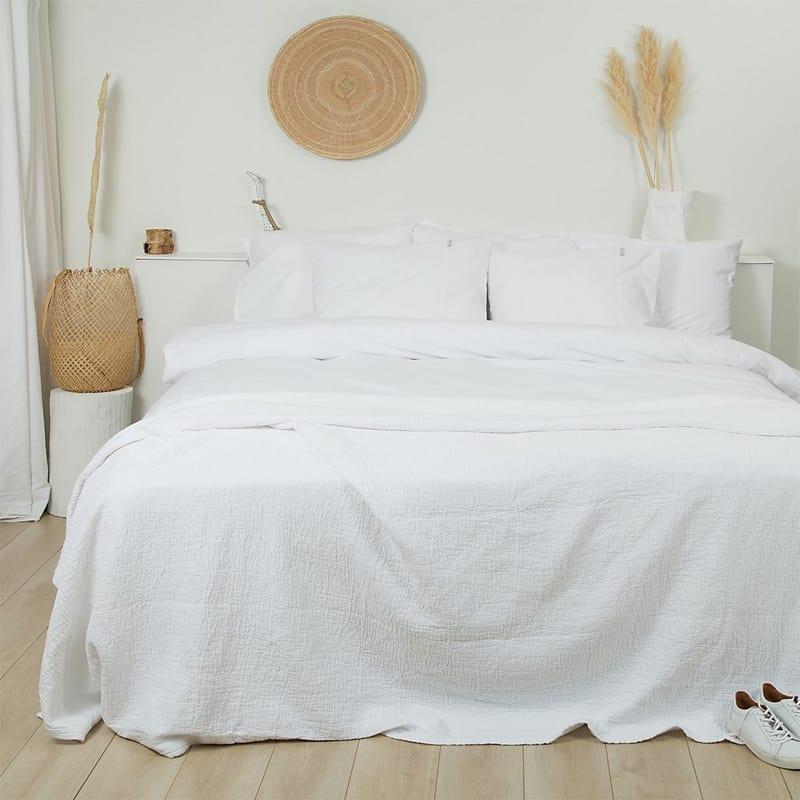 lichte slaapkamer met wit beddengoed en ecru muren