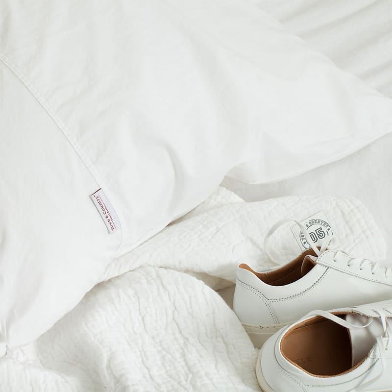 witte schoenen op sprei met wit katoen dekbedovertrek