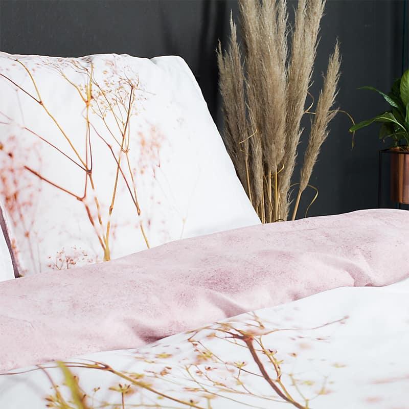bed met planten op achtergrond en gebloemd satijnen dekbedovertrek - gekleurde dekbedden