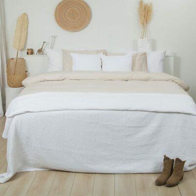 slaapkamer met houten vloer en wit bed met wit-zand dekbedovertrek