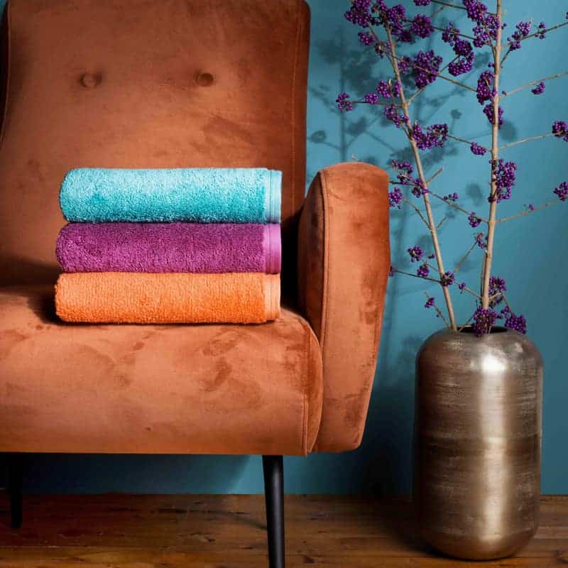 oranje stoel met drie gekleurde badhanddoeken van hotel kwaliteit