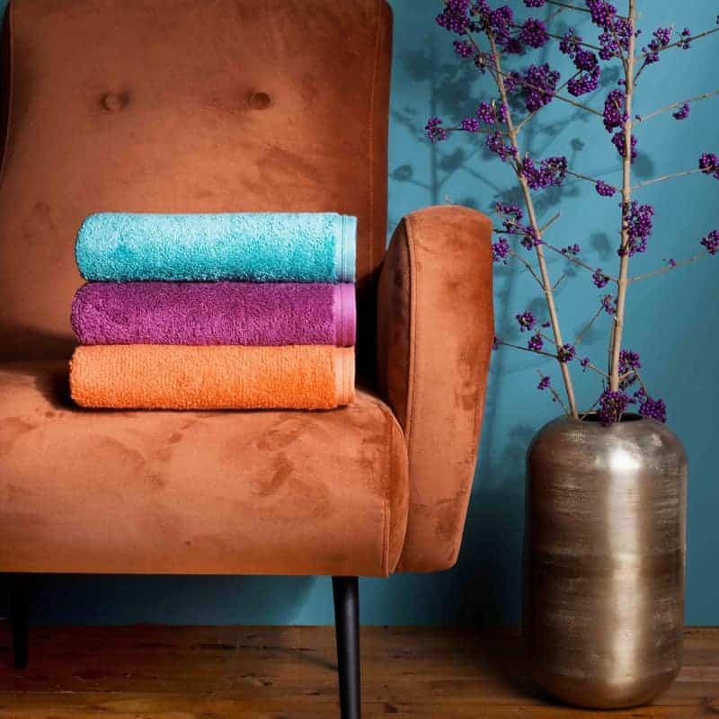 gekleurde douchelakens op oranje stoel, plant met vaas en blauwe muur