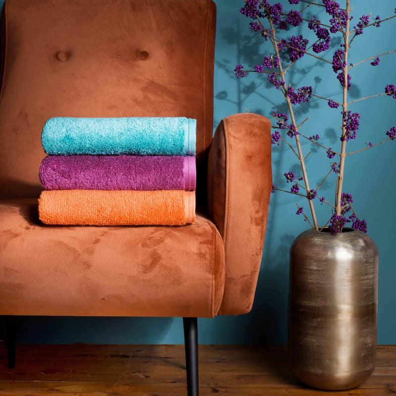 roest gekleurde suède fauteuil met vaas en luxe handdoeken in oranje, roze en blauw