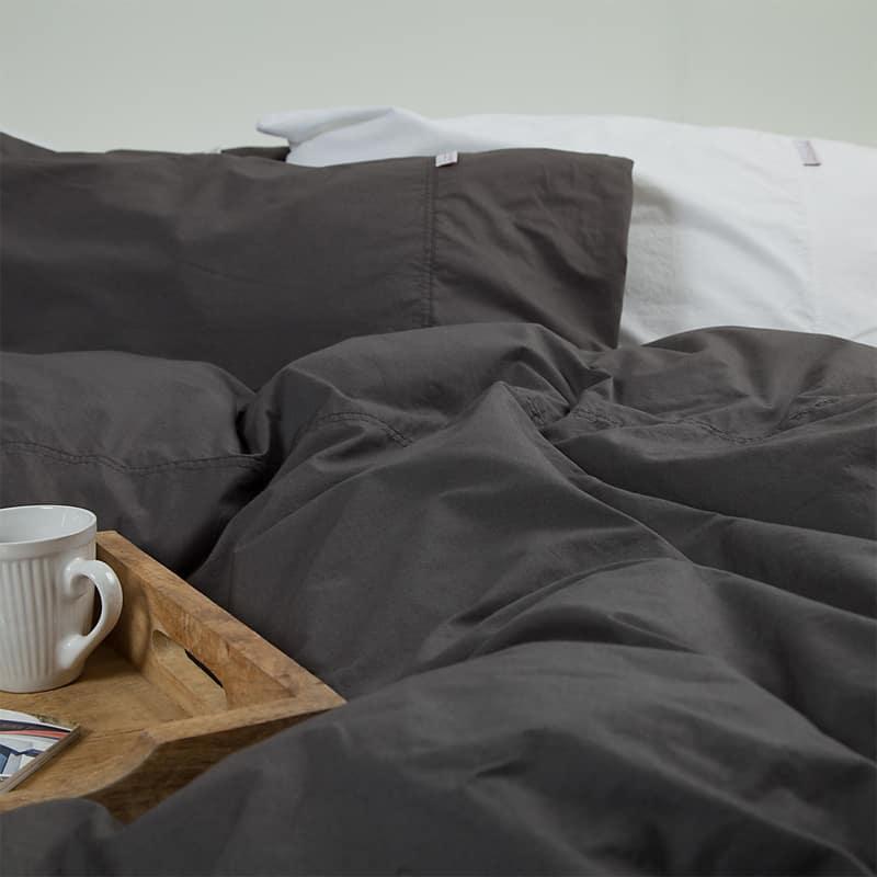 bed met zacht antraciet dekbedovertrek en koffie op een houten plankje