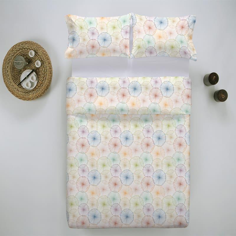 bed van boven af met twee kussens en luxe dekbedovertrek met kleuren in grappig motief