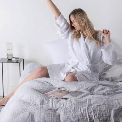 vrouw op bed met grijs katoenen dekbedovertrek