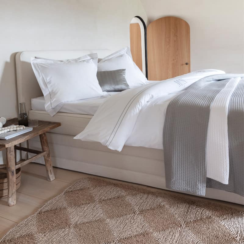 luxe opgemaakt bed met wit en grijs egyptisch katoen dekbedovertrek