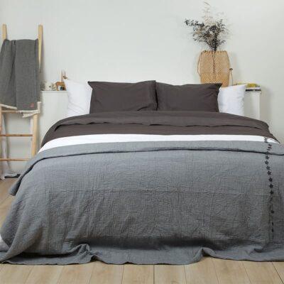 slaapkamer met houten vloer, grijze bedsprei en grijs dekbedovertrek broderie