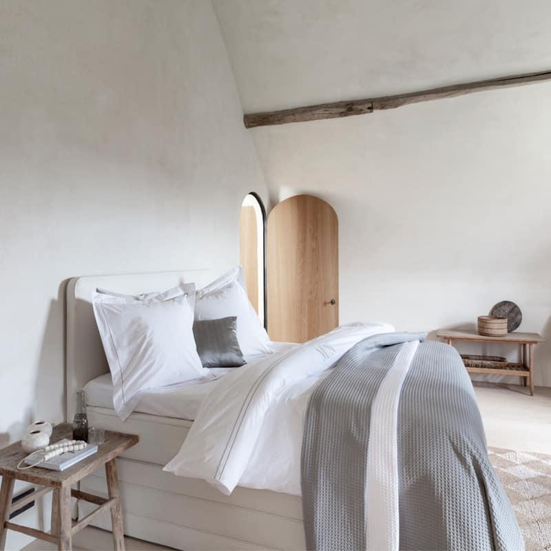 lichte slaapkamer met witte muren, bed mooi opgemaakt met egyptisch katoen luxe dekbedovertrek