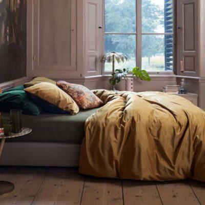 bed met houden vloer en fluwelen dekbed gold