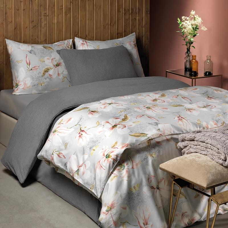 bed met grijs dekbedovertrek en kussens en satijnen bloemen dekbedovertrek combinatie