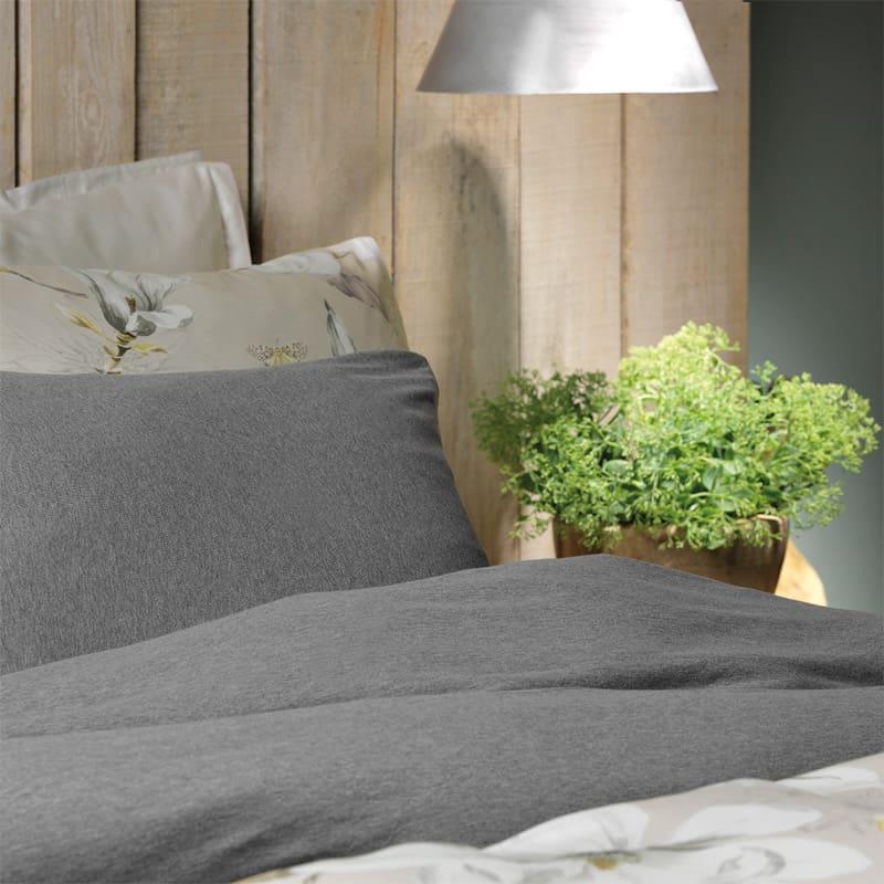 houten muur, grijs dekbedovertrek samen met bloemen