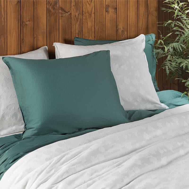 bed met groene en witte kussens