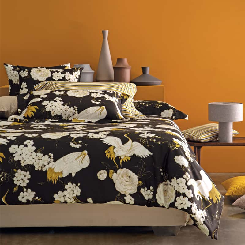 bed met zwart dekbedovertrek en oranje muur